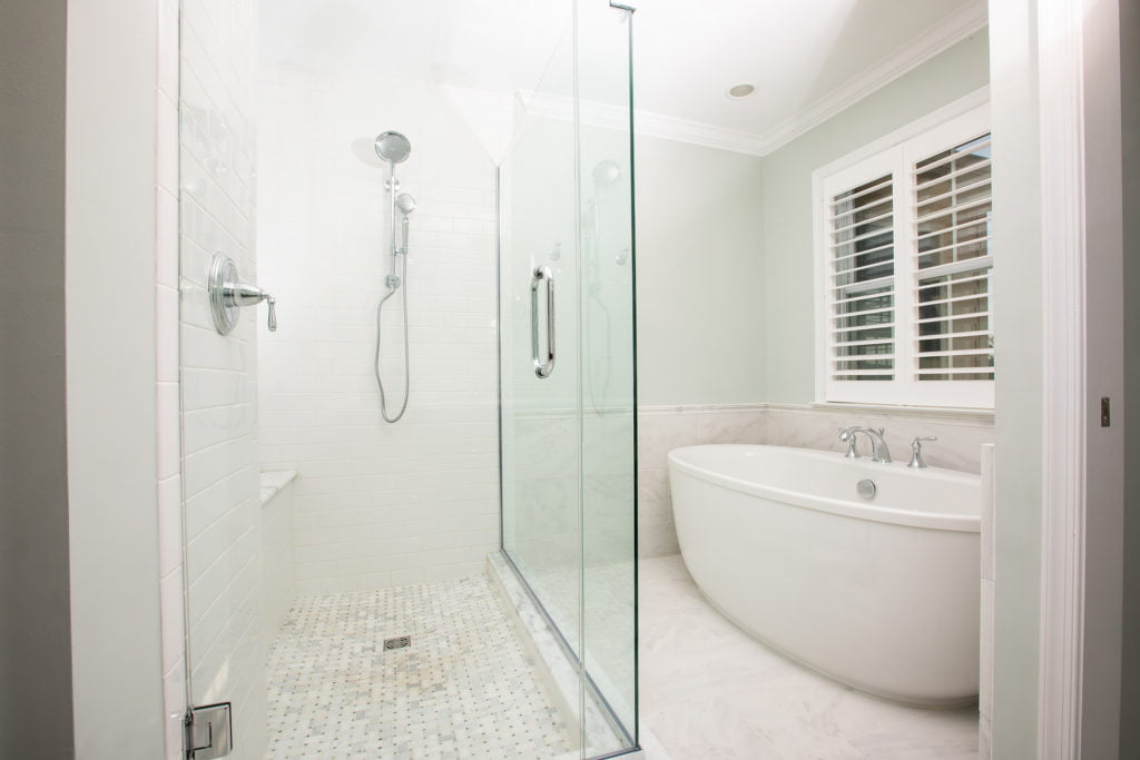 new bathroom remodel with glass shower and standing tub