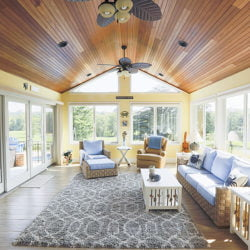 three season sunroom with wood ceilings and beachy furniture