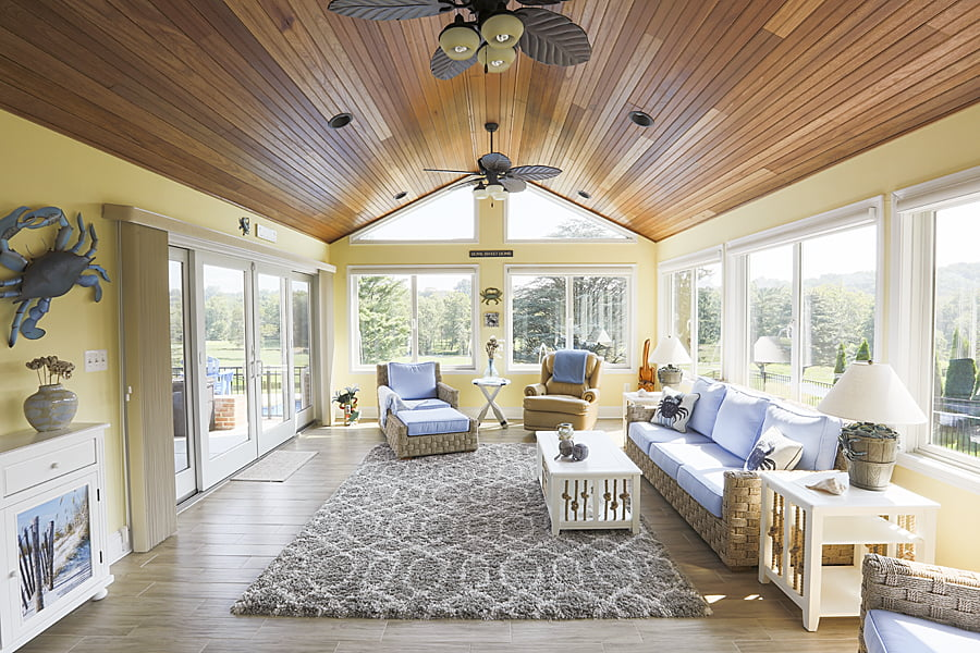 three season sunroom with wood ceilings and beachy furniture
