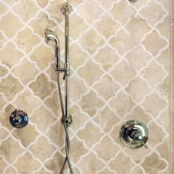 close up shot of newly installed shower faucet in master bathroom remodel