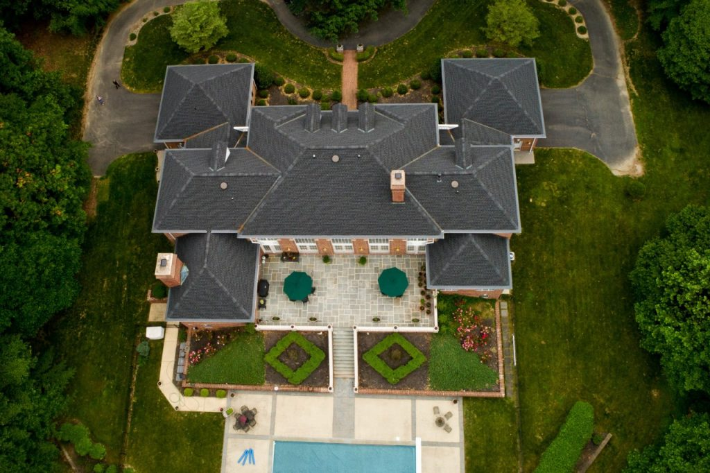 Large mansion style home with outside patio, pool, and garden topiaries